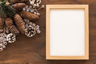 Blank frame with big cones on table