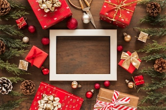Blank frame with bright gifts on table