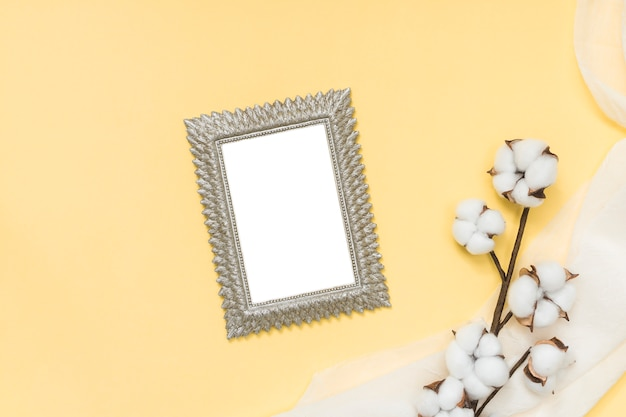 Blank frame with cotton branch on yellow table