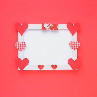 Blank frame with different hearts on table
