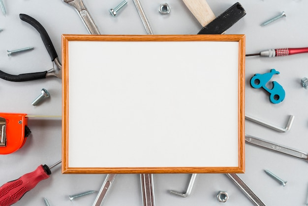 Blank frame with different tools on table