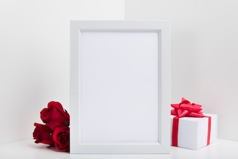 Blank frame with gift box and red roses