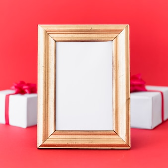 Blank frame with gift boxes on table