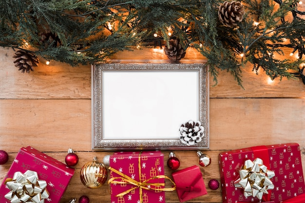 Blank frame with green branches on table