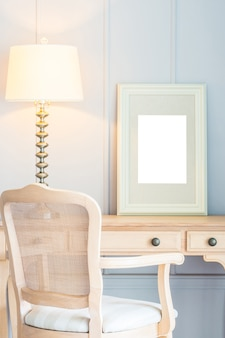 Blank frame with light lamp decoration on table