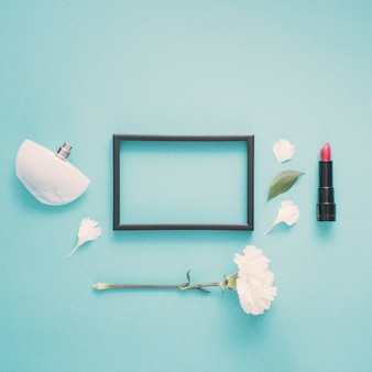 Blank frame with lipstick and flower on table