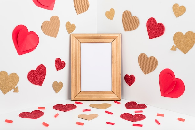 Blank frame with paper hearts on table