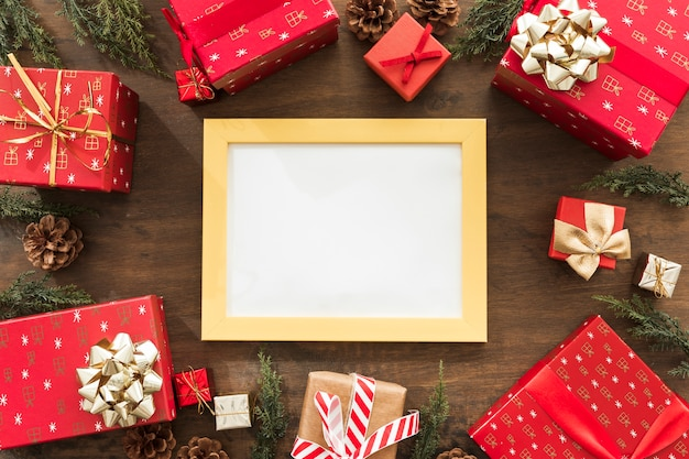 Blank frame with red gift boxes on table