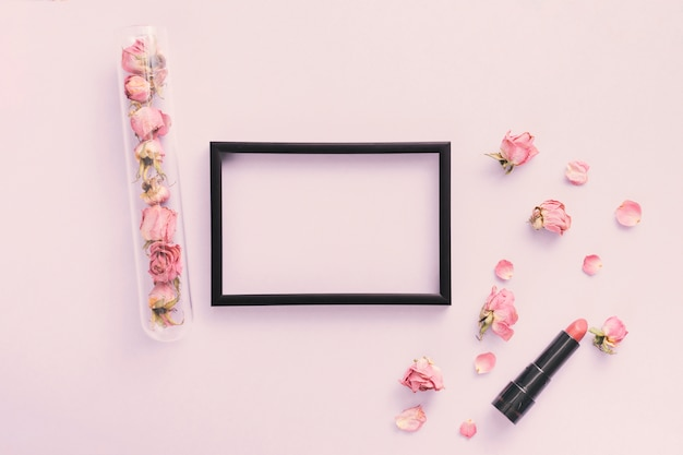 장미 꽃잎과 테이블에 립스틱 빈 프레임
