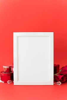 Blank frame with roses on table