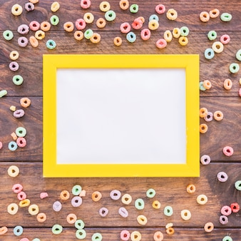 Blank frame with scattered cereals on table