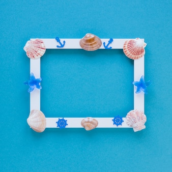 Blank frame with sea shells on table