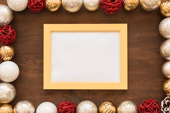 Blank frame with shiny baubles on table