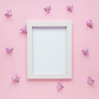 Blank frame with small purple flowers on table