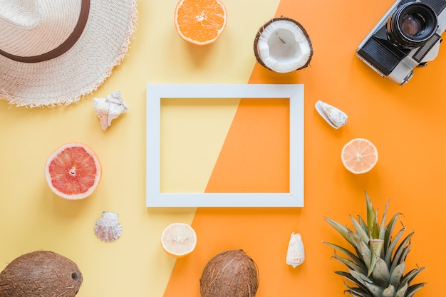 Blank frame with travel accessories, fruits and shells