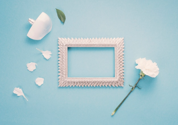Blank frame with white flower and perfume