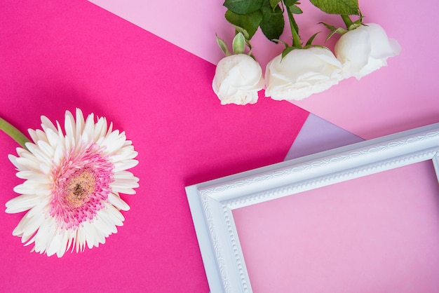 Blank frame with white flowers on table
