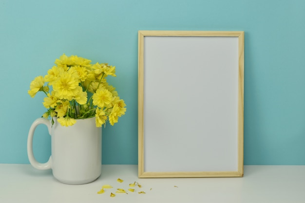 Blank frame with yellow flowers in vase.