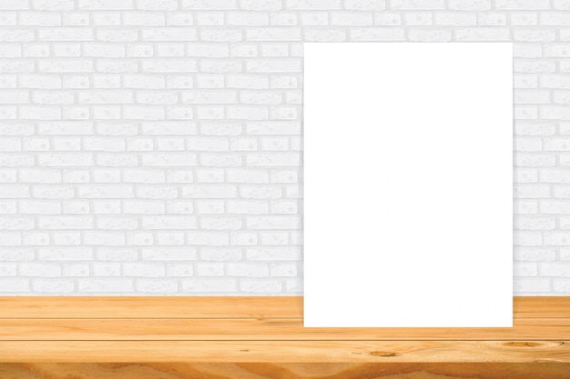 Blank frame on wooden table at white tile wall