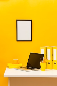 Blank frame on yellow wall front view