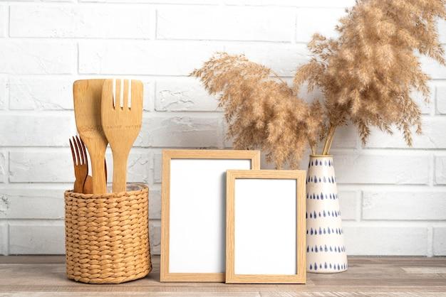 Cornici vuote accanto al vaso e agli utensili da cucina