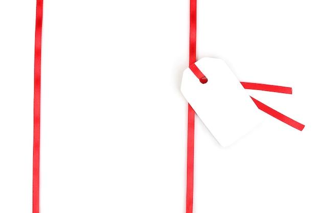 白で隔離の赤いサテンリボンの空白のギフトタグ
