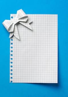 파란색 배경에 종이 활로 묶인 빈 선물 태그