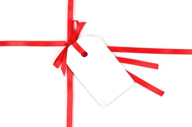 Пустая подарочная бирка с бантом на красной атласной ленте, изолированной на белом