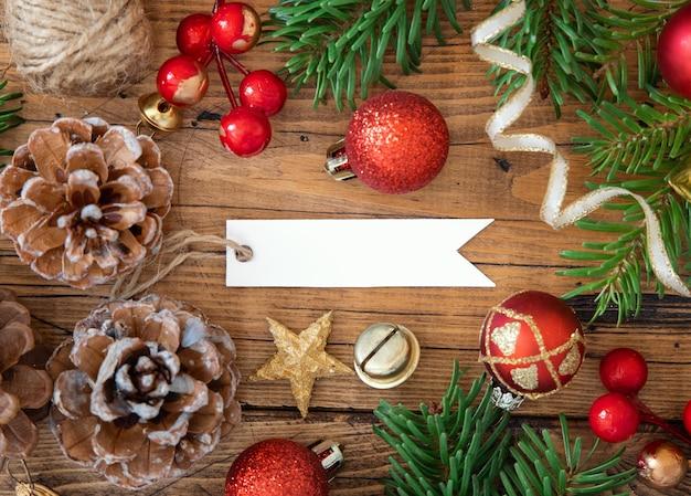 Пустая подарочная бирка с рождественскими украшениями вокруг вида сверху, макет