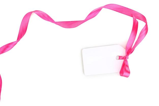 Пустой подарочный тег с розовым атласным бантом и лентой, изолированными на белом