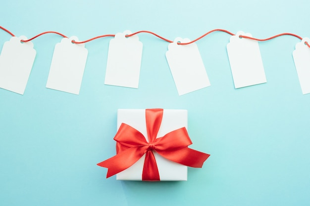 Blank gift tags mock-ups with red ribbon and gift box with bow on blue background. discount or sale concept.