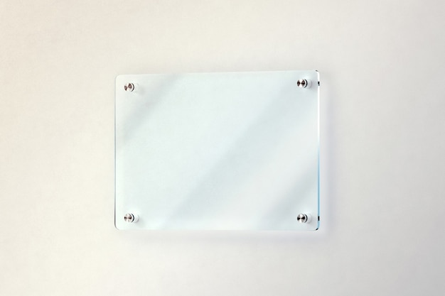 Blank glass door plate mounted on the wall