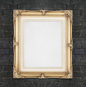 Blank gold color vintage photo frame hanging on black brick wall,template for adding your photo