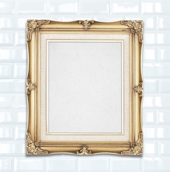Blank gold color vintage photo frame hanging on white ceramic tile wall,template for adding your photo