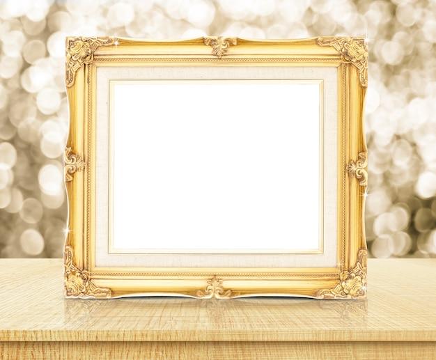 Пустая золотая старинная фоторамка с искрящимся золотом bokeh стена и деревянный стол