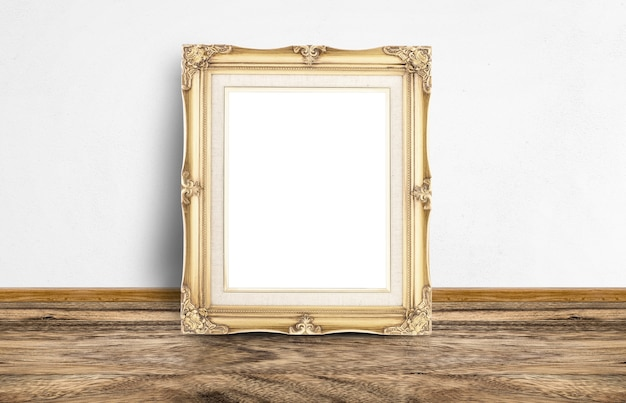 Blank golden vintage picture frame leaning at rustic wooden floor