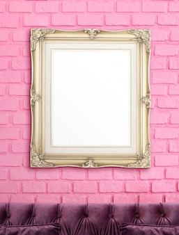 Blank golden vintage victorian style picture frame hanging on pink brick wall over luxury purple sofa