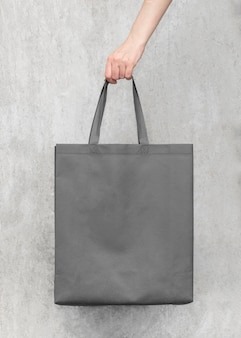 Blank gray canvas bag on concrete wall background, design mock up with hand. bags for shopping.