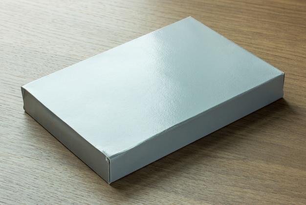 ダークウッドの背景に空白の灰色の紙箱