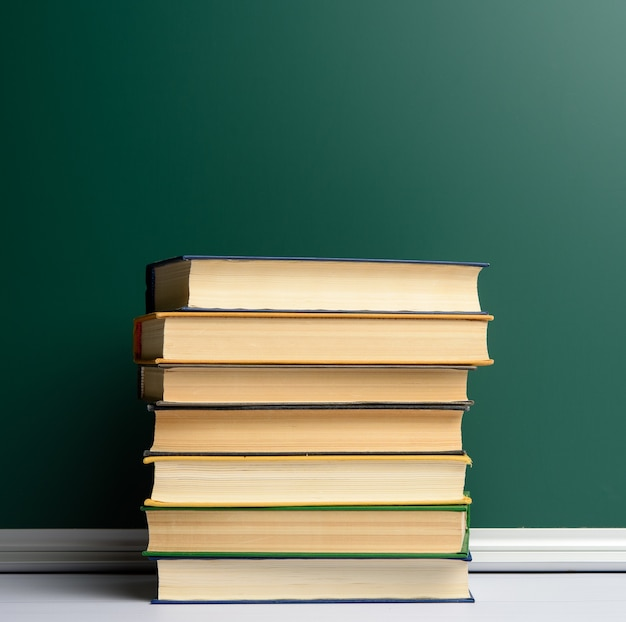 Blank green chalk school board and stack of books, back to school, copy space