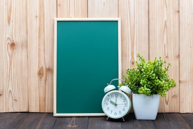 Blank green chalkboard and little tree vintage alarm clock on wood