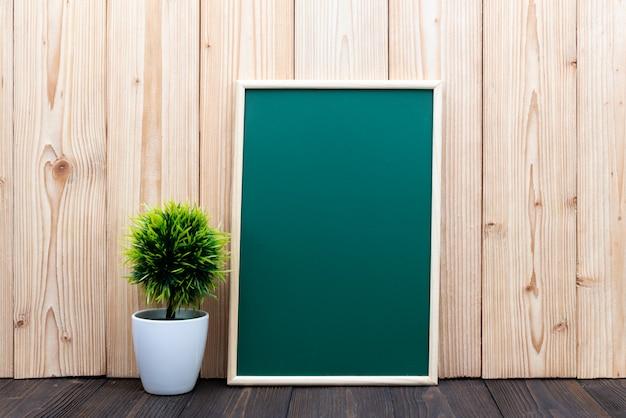 Blank green chalkboard and little tree on wood