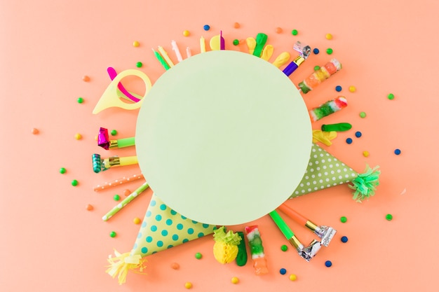Blank green frame over party accessories and candies on orange backdrop