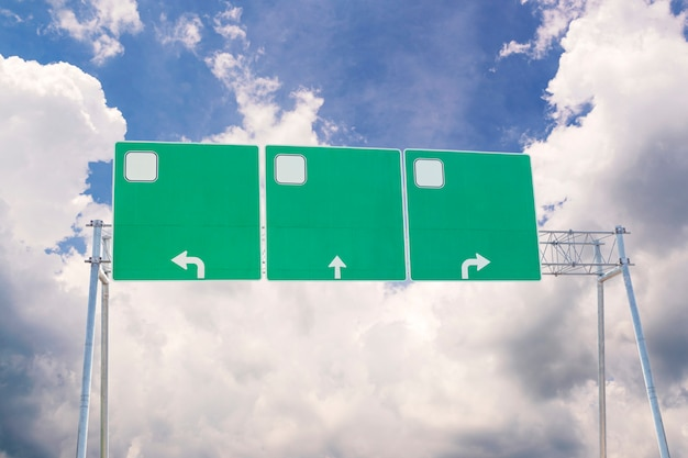 Blank green traffic road sign on sky and clouds background