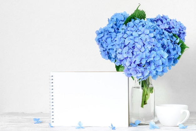 空白のグリーティングカードと白い木製のテーブルの上のコーヒーカップと青いアジサイの花