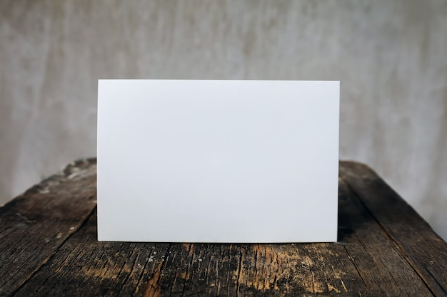 Пустая открытка на деревянном винтажном столе и фоне стены, письмо макет