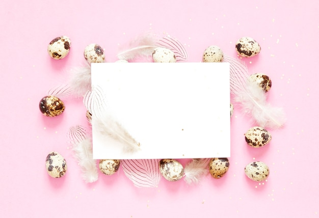 Blank greeting card. easter composition with easter eggs and feathering on pink background.