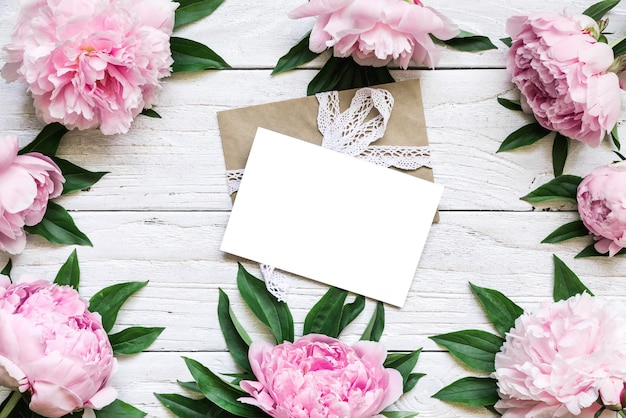 Blank greeting card iand envelope in frame made of pink peony flowers over white wooden table with copy space