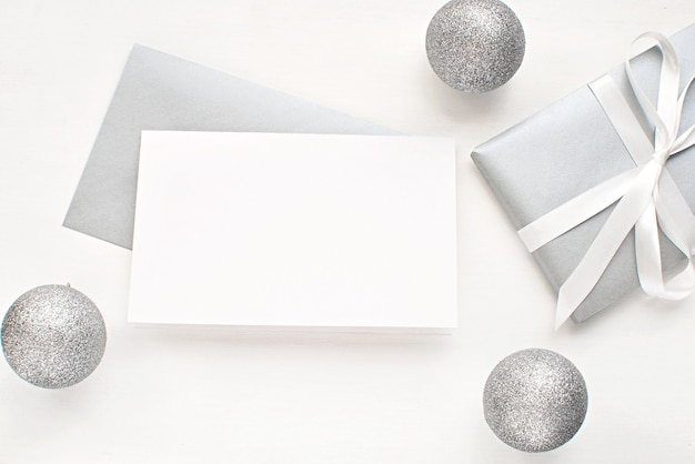 Blank greeting card, invitation with silver envelope and gift for christmas.