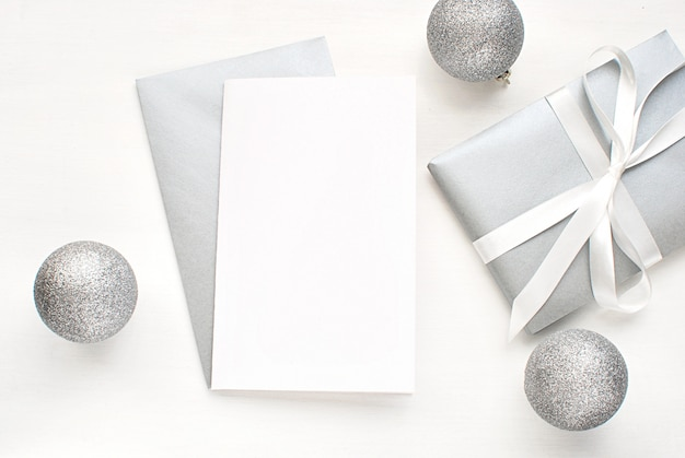 Blank greeting card, invitation with silver envelope and gift and decorations for christmas.